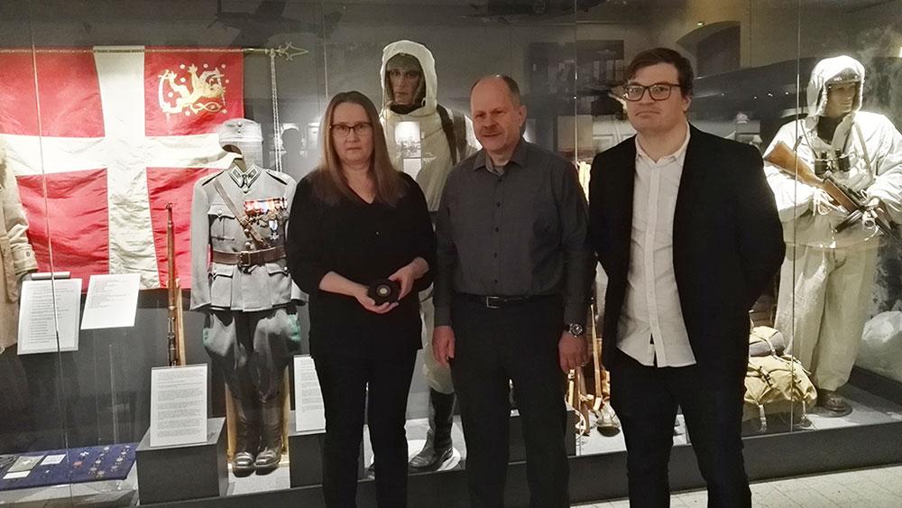 Vitriini, jossa on Häyhän sotilaspuku oli taustana, kun kultamitalit luovutettiin sotamuseon johtajalle ja Häyhän sukulaisille.